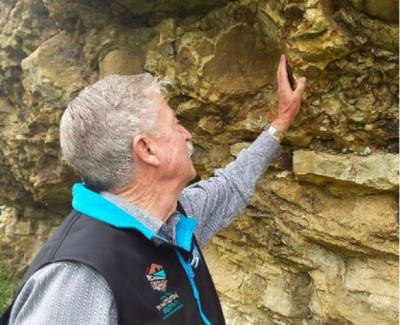 Mike Grey, farmer, resting his hand on a limestone outcrop