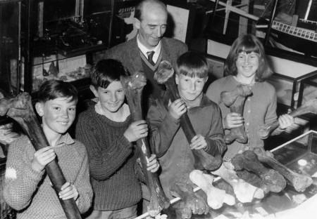 Pioneer Gallery custodian Neville F Turner with school children and moa bones. Waitaki District Archive 4444
