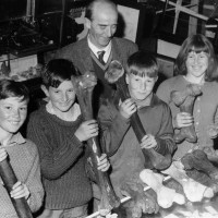 Pioneer Gallery custodian Neville F Turner with school children and moa bones. Waitaki District Archive 4444