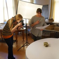 Image – Gina Buckley (photographer) and Rebecca Anderson (Gallery and Museum Technician) photographing Museum objects. February 2019